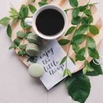 flat lay photography of leaves with cup of coffee and three macarons on chopping board